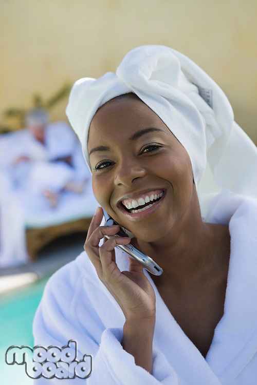 Portrait of woman in bathrobe using mobile phone