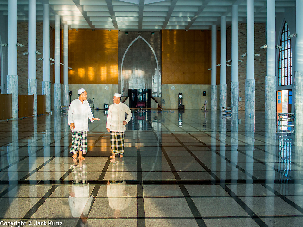 Men walk through the Songkhla Central Mosque on Eid al-Fitr. This is the largest mosque (called a Masjid in Thailand) in Songkhla province of Thailand. It is in a small community about midway between Hat Yai, the largest city in Songkhla, and the provincial capital, also called Songkhla. Eid al-Fitr is also called Feast of Breaking the Fast, the Sugar Feast, Bayram (Bajram), the Sweet Festival and the Lesser Eid, is an important Muslim holiday that marks the end of Ramadan, the Islamic holy month of fasting.