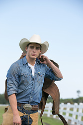 All American cowboy carrying a saddle over his shoulder on a ranch