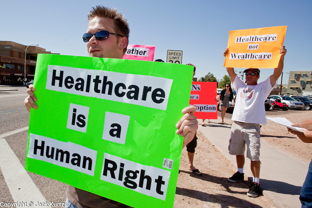 Aug. 8, 2009 -- SCOTTSDALE, AZ: JUSTIN MICKEY, a RN in Scottsdale, AZ, and other health care workers conduct a small rally in support of President Obama's health care plan Saturday. Five health care professionals demonstrated in favor of health care reform. Nearly 1,000 people opposed to the President Barack Obama's health care reform efforts picketed the offices of Congresman Harry Mitchell (D-AZ) in Scottsdale, AZ, Saturday. The protest was organized by conservative groups who are organizing similar protests against President Obama across the US. Ostensibly concerned mostly with health care reform, it was also a protest against almost everything related to the Obama administration. Photo by Jack Kurtz / ZUMA Press