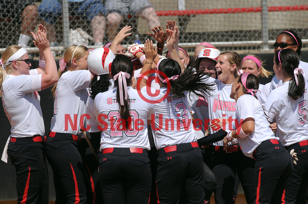 Softball team celebrates a run.
