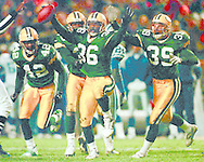 (Published caption 11/3/97) LeRoy Butler (36) celebrates his fourth-quarter interception with teammates Darren Sharper (42), Doug Evans (behind Butler) and Mike Prior.  Butler had another interception on the game's final play.