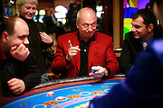 Casino owner Michael Boettcher sits among gamblers at his casino, Jazz Town, in central Moscow 18 October, 2006..Boettcher is the English CEO of Storm International, which operates the Super Slots chain, Moscow's Shangri La and Jazz Town, and several others..Storm International called off plans for an initial public offering after the Russian government announced legislation, expected to cruise through the State Duma next month, that will empower the state to handpick companies to operate inside four zones where gambling will remain legal after 2009. .When the state takes control of the gambling industry, foreigners will have an advantage over Russians thanks to Kremlin legislation that will make investments risky. .Soviet era gambling was limited to lotteries with modest prizes and a few outdoor gaming tables. Today the slot machine arcades around every Moscow metro station and the bright lights of the casinos on the Novy Arbat tell the story of raging leisure spending in the Russian capital. .