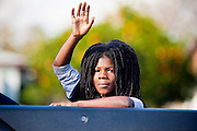 16 JANUARY 2012 - MESA, AZ:  A boy waves from a float in the parade on Martin Luther King Day in Mesa, AZ, Monday, Jan. 16. Hundreds of people participated in the parade which marched through downtown Mesa.   PHOTO BY JACK KURTZ