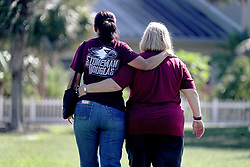 Marjory Stoneman Douglas teachers Connie Forti and Diana Cortez walk arm-in-arm after viewing the Parkland Heart Project at Pine Trails Park in Parkland, Fla., commemorating all 17 of the victims killed last year at the school. Photo by Mike Stocker/Sun Sentinel/TNS/ABACAPRESS.COM
