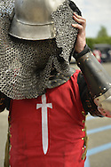 Garden City, New York, U.S. - June 14, 2014 - SAM AWRY is a USA Knights member putting on his helmet with chainmail protection, wearing warrior combat sport armor  at Eternal Con, the annual Pop Culture Expo, with costumes, Gaming, Sci-Fi, Cosplay, Horror, and held at the Cradle of Aviation Museum on Long Island. Armored Combat League members compete in international medieval combat competitions.