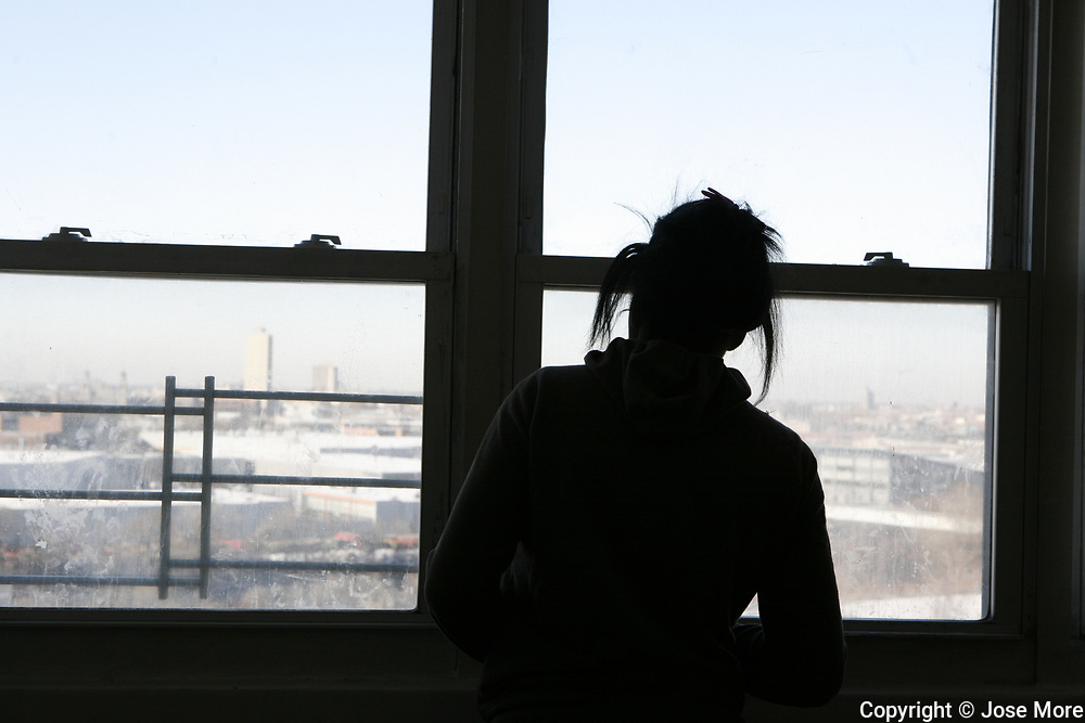 Rose Ricks, 17, looks out the window of her Cabrini Green apartment a day before they moved out. Long time  resident Annie Ricks and her family pack up their belongings in their apartment. The Ricks' were the last residents in the public housing building. Ricks moved on Thursday December 9, 2010.<br /> Photography by Jose More