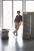 Young man standing by packages in empty office