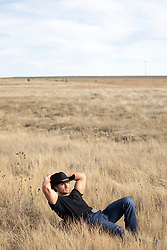 cowboy taking time off and relaxing in a beautiful field