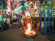 """17 AUGUST 2016 - BANGKOK, THAILAND: A man burns """"ghost money"""" in front of his home during the Ghost Festival in the Chinatown section of Bangkok. The Ghost Festival is a Buddhist and Taoist holy day celebrated on the 15th day of the 7th lunar month. It is primarily celebrated in China and Chinese communities beyond China. In Thailand, it's celebrated in Thai-Chinese communities in Bangkok, Phuket and Chiang Mai.  On that day ghosts and spirits, including those of the deceased ancestors, come out from the lower realm to visit the living. Families prepare elaborate banquets for the spirits and burn """"ghost money"""" for the spirits to use in the other realm. It is a day for venerating dead relatives.     PHOTO BY JACK KURTZ"""