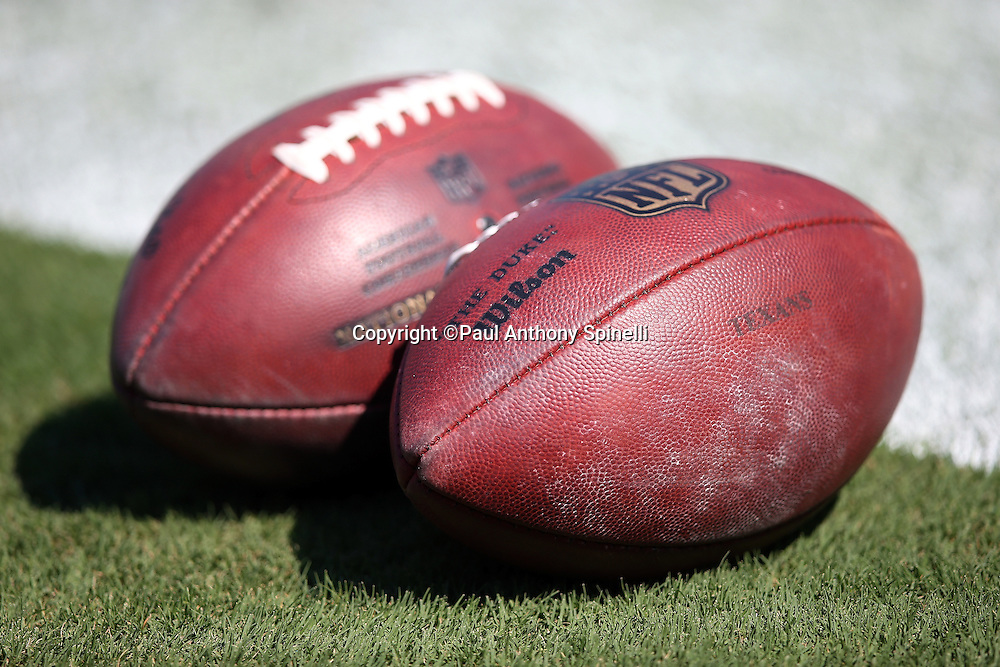 Two footballs lie on the grass during the Carolina Panthers 2015 NFL week 2 regular season football game against the Houston Texans on Sunday, Sept. 20, 2015 in Charlotte, N.C. The Panthers won the game 24-17. (©Paul Anthony Spinelli)