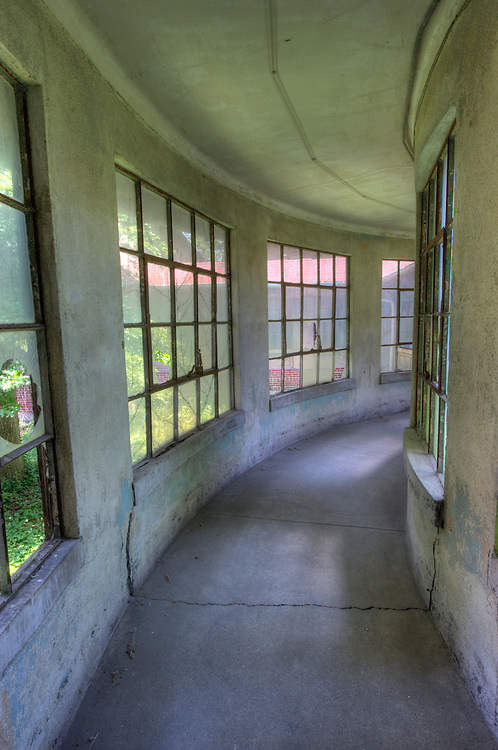 In 1990, the Ellis Island Immigration Museum opened on the island's north side.  However, some thirty buildings on the south side remain un-restored.  High Definition Range (HDR) image..This is a hallway that connects the buildings at Ellis Island South, New York (US).