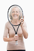 Portrait of senior woman holding tennis racket in front of her face against white background