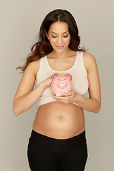 Pregnant woman holding piggy bank (Credit Image: © Image Source/ZUMAPRESS.com)