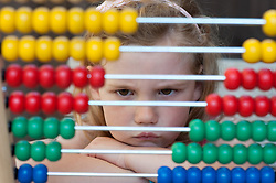 Young girl (6 years) looking fed up behind an abacus during homework. *MODEL RELEASED*