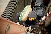 Eddy Acosta, a mason with D&R Masonry Restoration, carries sand up a ladder while working on a balcony resurfacing job at the Lexington Apartments in downtown Portland Monday.