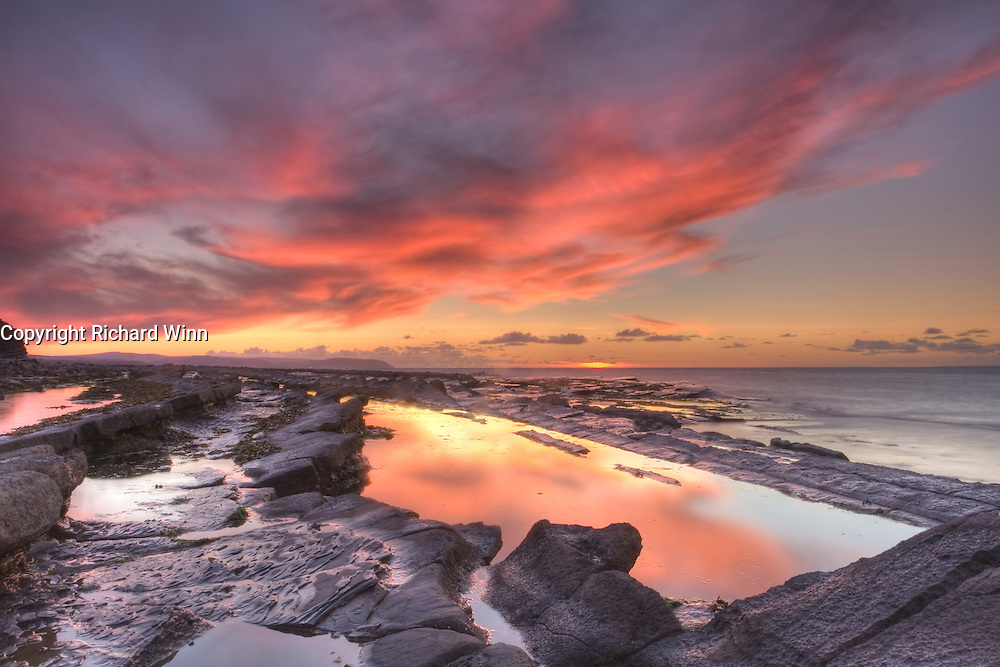 The last rays of the setting sun produced vivid pinks and oranges in the sky over Kilve Beach. Use of a 3 stop reverse ND graduated filter and a warming polariser evened up the exposure and maintained the reds. Gentle use of HDR recovered the reflections in the rock pools, without making it look unnatural.