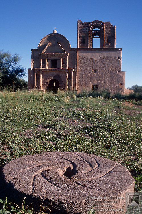 Stone used to grind grain for Tumacacori mission, visible behind, Tumacacori, Arizona..Rights & Usage:.No rights granted. Subject photograph(s) are copyrighted by Edward McCain/McCain Photography. All rights are reserved except those specifically granted in writing prior to any use...McCain Photography.211 S 4th Avenue.Tucson, AZ 85701-2103.(520) 623-1998.mobile: (520) 990-0999.fax: (520) 623-1190.http://www.mccainphoto.com.edward@mccainphoto.com