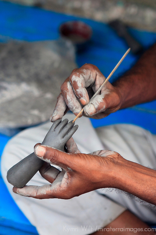 Hands working on a hand in the potter's village of Kumartuli in Calcutta.