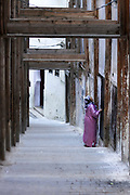 FEZ, MOROCCO - 01st NOVEMBER 2013 - Woman wearing a colourful dress and headscarf knocks on the door of a house in the old Fez Medina, Middle Atlas Mountains, Morocco.
