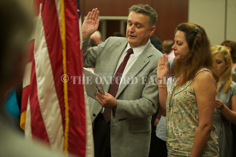 Gokhan Karahan (left), originally from Turkey, and his wife Lorena Fonseca, originally from Brazil, take the oath of citizenship during a Naturalization Ceremony in federal court in Oxford, Miss. on Friday, March 29, 2012.  Forty-nine people took the oath.