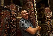Albert Borokhim repositions a Persian Bijar rug inside his store on Monroe Street, Monday, April 24, 2017.