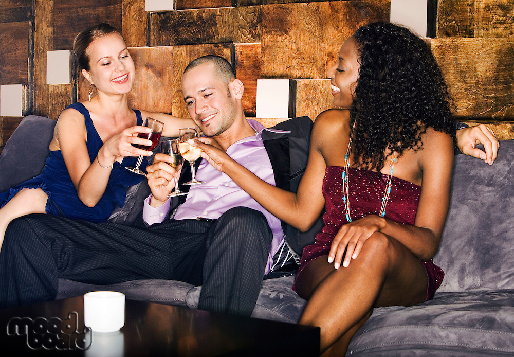 Man with two women toasting sitting on couch in bar