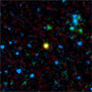 This false-colour image from NASA's Spitzer Space Telescope shows a distant galaxy (yellow) that houses a quasar, a super-massive black hole circled by a ring, or torus, of gas and dust. Spitzer's infrared eyes cut through the dust to find this hidden object, which appears to be a member of the long-sought population of missing quasars. The green and blue splotches are galaxies that do not hold quasars. In this image, infrared data from Spitzer is coloured both blue (3.6 microns) and green (24 microns), and radio data from the Very Large Array telescope is coloured red. The quasar-bearing galaxy stands out in yellow because it emits both infrared and radio light.