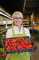 Portrait of a senior woman with red chili peppers in market