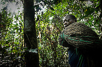 Carrying hunting nets through the Okapi Wildlife Reserve, Ituri Rainforest, DR Congo