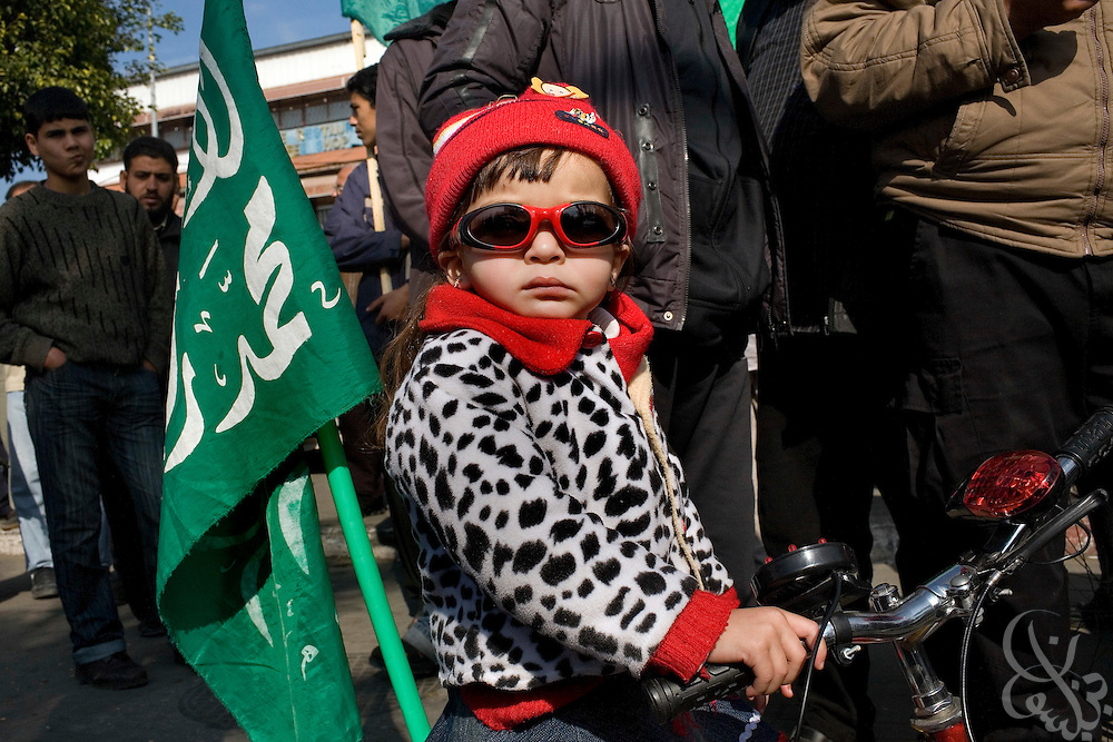 "A Palestinian girl rides a bicycle adorned with a HAMAS flag during a ""Victory"" parade thrown by militant Palestinian political group HAMAS January 20, 2009 in Gaza City. Several thousand marchers celebrated what HAMAS called the defeat of Israel during the recent 21 day offensive by Israeli forces against HAMAS fighters. During the operation more than 1500 Palestinians were killed and more than 4000 homes destroyed in the narrow Gaza Strip..."