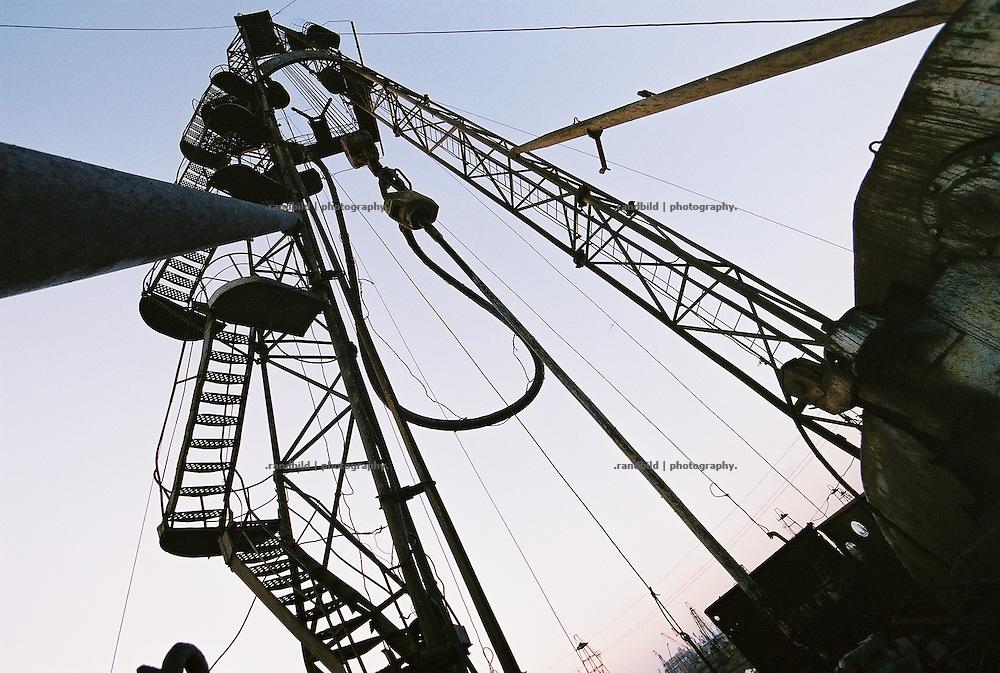 Das Selimkhanow-Ölfeld im Licht der aufegehnden Sonne. Vor über 100 Jahren begann hier im Süden der aserbaidschanischen Hauptstadt Baku der erste Ölboom. Noch immer fördern hier Arbeiter Erdöl mit abenteuerlich alter Technik das schwarze Gold aus dem Untergrund. Überall rosten alte Bohrtürme vor sich hin, schwarze Seen aus Öl verseuchen die Landschaft. Abwässer werden in das nahe gelegegen Kaspische Meer geleitet. Eine apokalyptische Landschaft...Selimkhanov oil field at dawn near Baku, aserbaijan.