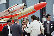 An Aerospatiale salesman and potential buyers surrounded by jet fighters and missiles at the Paris Air Show, at Le Bourget Airport, France. Held every other year, the event is one of the world's biggest international trade fairs for the aerospace business.