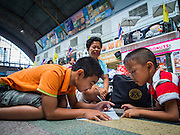 16 APRIL 2014 - BANGKOK, THAILAND: Boys do their homework on the floor of Hua Lamphong Railway Station, the main train station in Bangkok. They were waiting to catch a train to take them home after visiting family for the Songkran holiday in Bangkok. Thai highways, trains and buses were packed Wednesday as Thais started returning home after the long Songkran break. Songkran is normally three days long but this year many Thais had at least an extra day off because the holiday started on Sunday, so many Thais started traveling on Friday of last week.    PHOTO BY JACK KURTZ