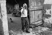 A farmer and shepherd with his dog in his barn near Ste-Croix-de-Caderle in the Cévennes, in the Gard departement in the south of France.