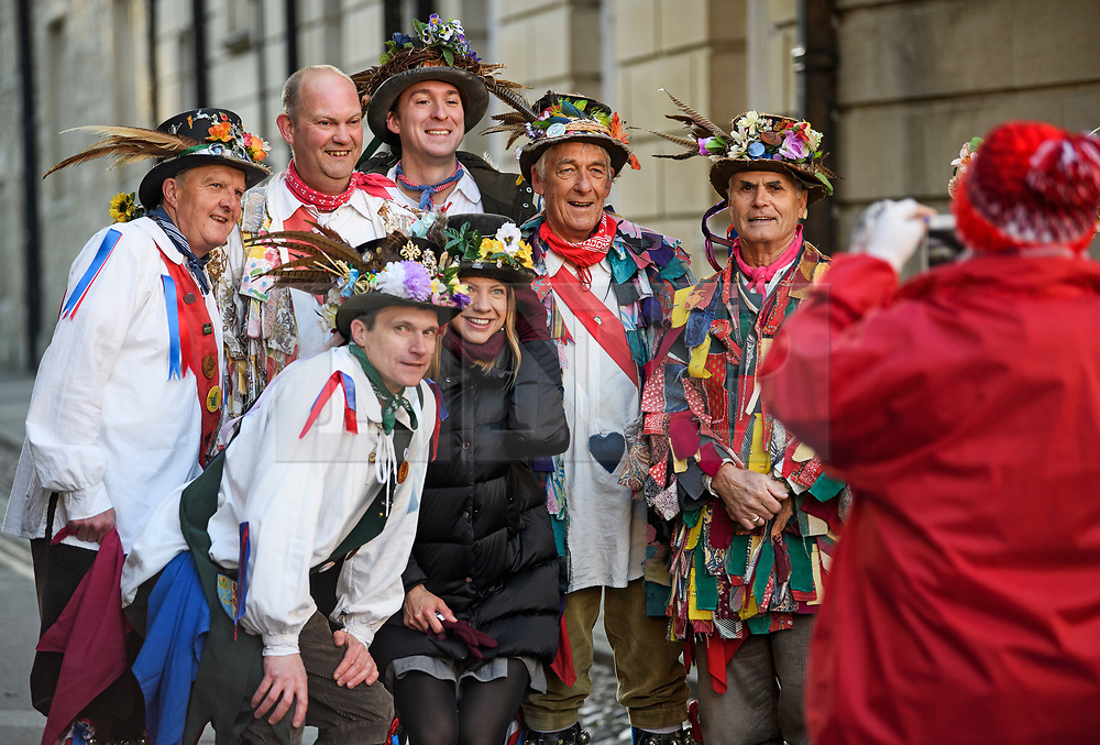 """© Licensed to London News Pictures. 01/05/2018. Oxford, UK. Morris dancers in dress pose for a photograph with a tourist as they prepare to dance next to Hertford Bridge, often called """"the Bridge of Sighs"""" in Oxford, Oxfordshire as part of May Day celebrations. Students were again prevented from jumping from Magdalen Bridge in to the river, which has historically been a tradition, due to injuries at a previous years event . Photo credit: Ben Cawthra/LNP"""