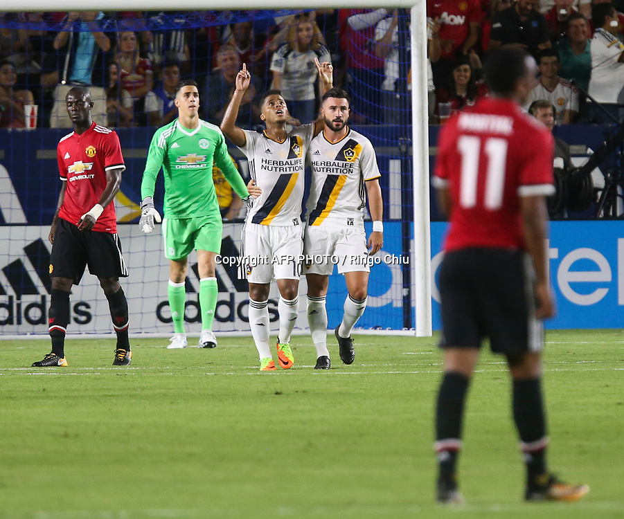 Los Angeles Galaxy Giovani dos Santos, center, celebrates his goal with teammate Romain Alessandrini, 2nd right, against Manchester United during the second half of a national friendly soccer game at StubHub Center on July 15, 2017 in Carson, California. The Manchester United won 5-2. AFP PHOTO / Ringo Chiu