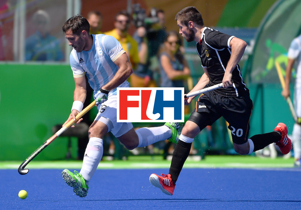 Argentina's Agustin Mazzilli (L) vies with Germany's Martin Zwicker during the men's semifinal field hockey Argentina vs Germany match of the Rio 2016 Olympics Games at the Olympic Hockey Centre in Rio de Janeiro on August 16, 2016. / AFP / Pascal GUYOT        (Photo credit should read PASCAL GUYOT/AFP/Getty Images)