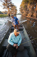 BOAT DRIVER AND ANGLER RIDING IN A BOAT THROUGH CADDO LAKE TEXAS