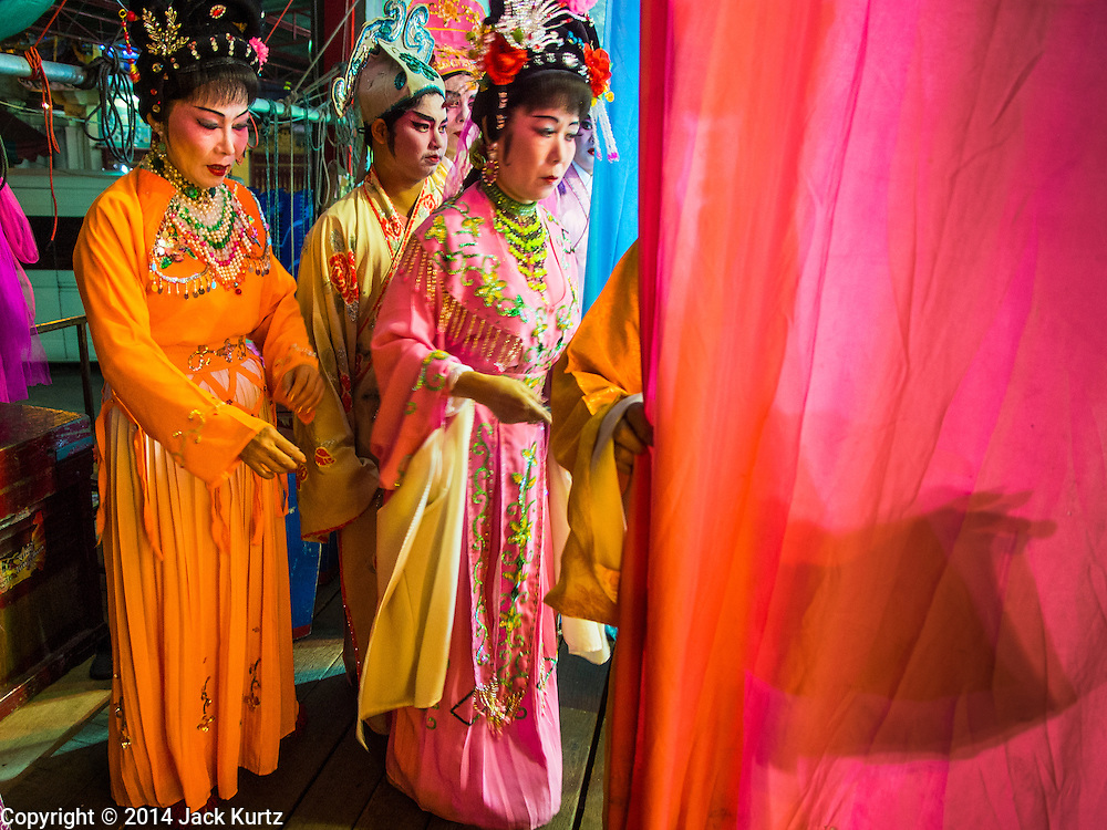 """06 DECEMBER 2015 - BANGKOK, THAILAND: Chinese opera performers wait in the wings before taking the stage at the Ruby Goddess Shrine in the Dusit district of Bangkok. Chinese opera was once very popular in Thailand, where it is called """"Ngiew."""" It is usually performed in the Teochew language. Millions of Chinese emigrated to Thailand (then Siam) in the 18th and 19th centuries and brought their culture with them. Recently the popularity of ngiew has faded as people turn to performances of opera on DVD or movies. There are about 30 Chinese opera troupes left in Bangkok and its environs. They are especially busy during Chinese New Year and Chinese holidays when they travel from Chinese temple to Chinese temple performing on stages they put up in streets near the temple, sometimes sleeping on hammocks they sling under their stage.     PHOTO BY JACK KURTZ"""