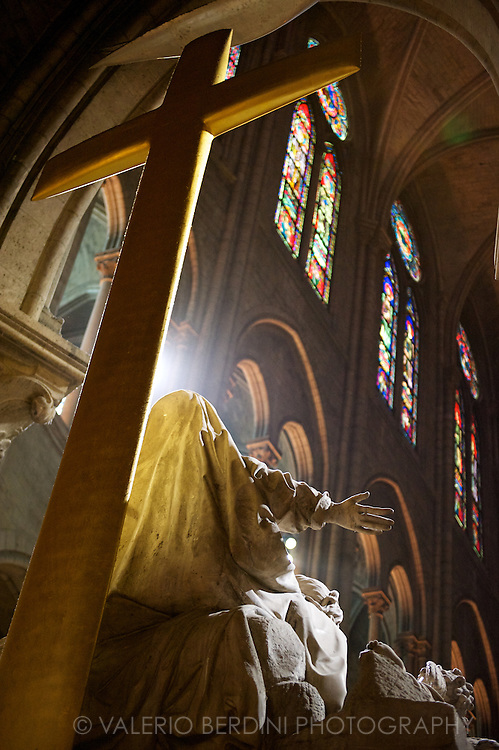 A ray of sun through a window hits a statue in a church of Paris.