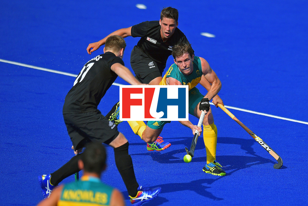 Australia's Fergus Kavanagh controls the ball as New Zealand's Stephen Jenness (L) and Nick Wilson (above) chase during the men's field hockey Australia vs New Zealand match of the Rio 2016 Olympics Games at the Olympic Hockey Centre in Rio de Janeiro on August, 6 2016. / AFP / CARL DE SOUZA        (Photo credit should read CARL DE SOUZA/AFP/Getty Images)