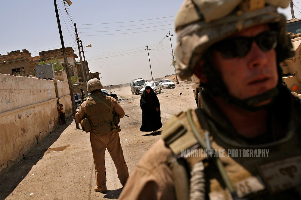 IRAQ, BASRA - JULY 5: An Iraqi woman walks towards SSgt. Patrick Hopwood (34) (R) of 1st Battalion 26th Brigade 2nd Division, from Miami, Florida, as he conducts a joint patrol with Iraqi soldiers in the poverty stricken neighborhood of Hayaniyah, July 5, 2008 in Basra, Iraq.  When British forces withdrew in 2007, Basra deteriorated into street battles between numerous Shiite militias and criminal gangs. In April 2008, Iraqi prime minister, Nouri al Maliki, sent two Iraqi army divisions to retake control of Basra. While the fighting has ended, unemployment is rife, at about 70 per cent. Since early 2008, Iraq's security situation has improved with oil production increasing, record government surplus and easing sectarian tensions. (Photo by Warrick Page)
