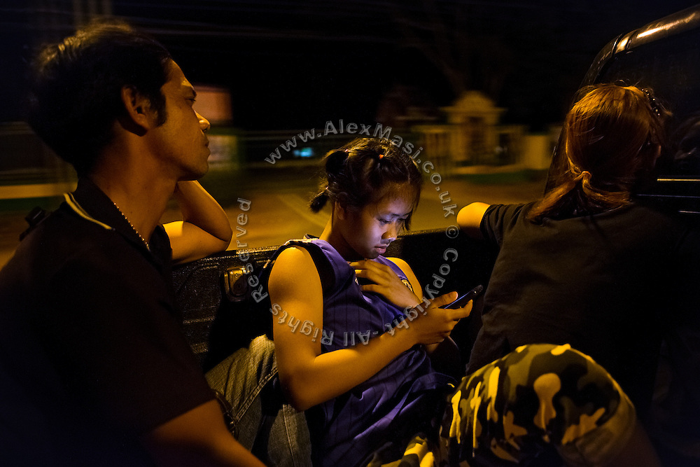Browsing on her mobile phone, Phatsorn Bunmasen, 14, is being driven to a Muay Thai boxing match, where she will fight in a local arena set up in a village near Ubon Ratchathani, northeast Thailand.