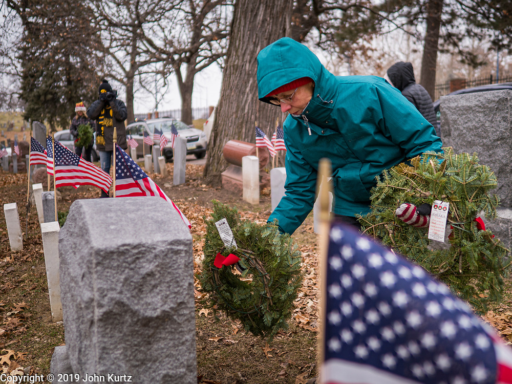14 DECEMBER 2019 - DES MOINES, IOWA: A volunteer places a Christmas wreath on a veteran's grave. Volunteers working with Wreaths Across America placed Christmas wreaths on the headstones of more than 600 US military veterans in Woodland Cemetery in Des Moines. The cemetery, one of the first in Des Moines, has the graves of veterans going back to the War of 1812.     PHOTO BY JACK KURTZ