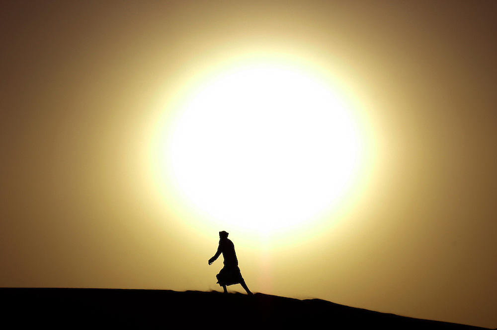 A desert safari tour driver walks over a sand dune at sunset in the United Arab Emirates.
