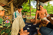 29 JUNE 2013 - BATTAMBANG, CAMBODIA:  Cambodian men who drive Bamboo Trains play cards in a hut at the terminal station near Battambang. The bamboo train, called a norry (nori) in Khmer is a 3m-long wood frame, covered lengthwise with slats made of ultra-light bamboo, that rests on two barbell-like bogies, the aft one connected by fan belts to a 6HP gasoline engine. The train runs on tracks originally laid by the French when Cambodia was a French colony. Years of war and neglect have made the tracks unsafe for regular trains.  Cambodians put 10 or 15 people on each one or up to three tonnes of rice and supplies. They cruise at about 15km/h. The Bamboo Train is very popular with tourists and now most of the trains around Battambang will only take tourists, who will pay a lot more than Cambodians can, to ride the train.       PHOTO BY JACK KURTZ
