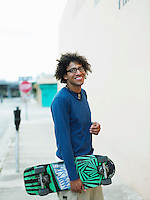 Young man carrying skateboard in street portrait