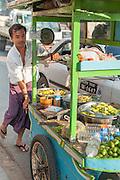 Fruit street vendor pushing his trolley in Yangon (Myanmar)