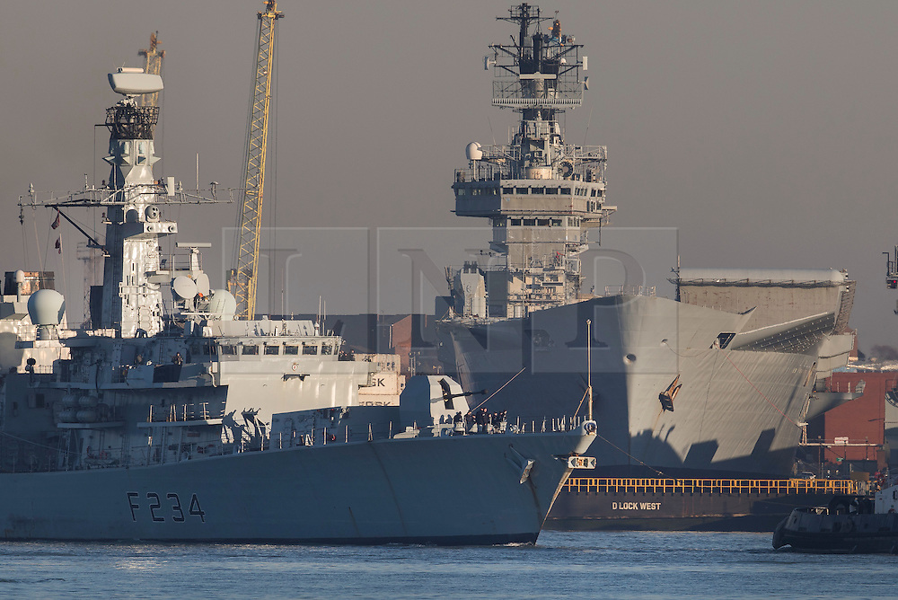 © Licensed to London News Pictures. 30/11/2016. Portsmouth, UK. HMS Iron Duke passes in front of the former Royal Navy aircraft carrier HMS Illustrious in dock, before she is moved out into the harbour ahead of her final voyage to a scrap yard.  The last of the Invincible Class carriers has been sold to the Leyal Ship Recycling and Dismantling company in Aliaga, Turkey - the same yard that dismanled Illustrious' sister ships Ark Royal and Invincible. Photo credit: Peter Macdiarmid/LNP